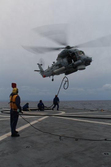 As part of their training they practiced Helicopter In-Flight Refuelling (HIFR for short). This sees the helicopter pick up the fuelling hose using its winch, and then refuel while it flies alongside the ship. This is often a much quicker way of refuelling the helicopter during certain naval operations and/or rough weather.